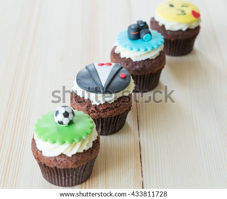 Delicious cupcakes with icons of ball, tuxedo, smiley and camera on it on wooden desk