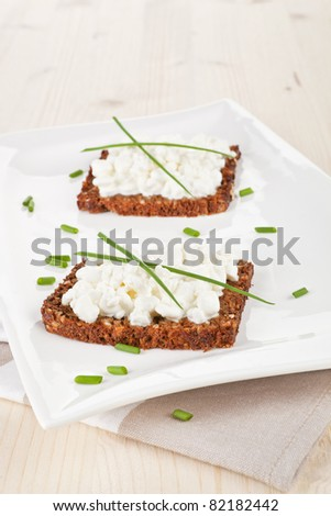 Delicious dark bread slices with cottage cheese and fresh herbs on white plate on wooden background.