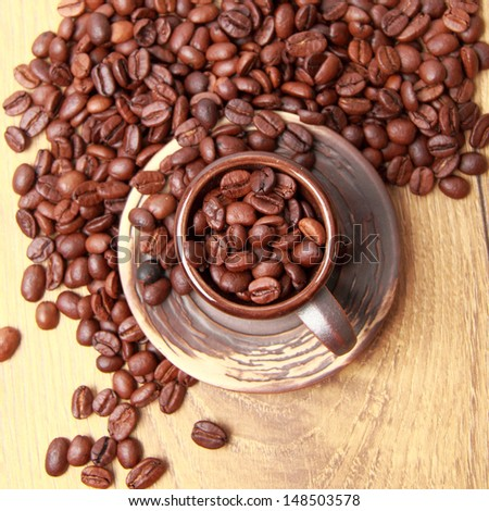 Delicious dark brown coffee beans in small ceramic coffee cup over light brown wooden background
