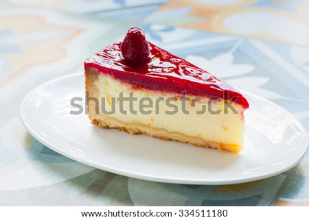 delicious , delicate cheesecake with raspberry sauce on a white plate . wooden background . close-up