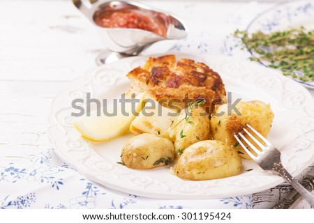 Delicious dinner: baked potatoes with thyme and cutlets, served with spicy tomato sauce. Selective focus - stock photo