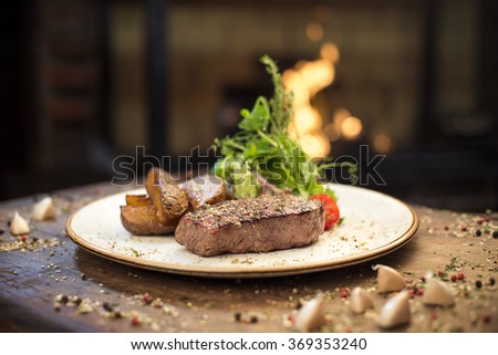 Delicious dinner with beef steak, potatoes and salad on a wooden table, near the fireplace  - stock photo