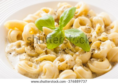 Delicious dish of tortellini with pesto in white plate