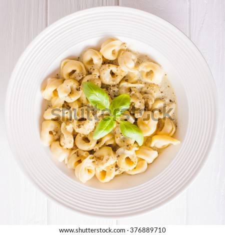 Delicious dish of tortellini with pesto in white plate. Top view - stock photo
