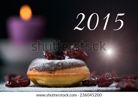 Delicious donut topped with chocolate and cranberries. Romantic atmosphere with text message, candle in background. Shallow depth of field. - stock photo