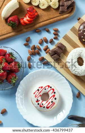 Delicious donuts. Served on the wooden board and white plate. Decorated with strawberry, banana, coconut and almond. Blue background. Silver knife and fork. Vertical image. Top view. View from above