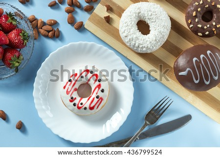 Delicious donuts. Served on the wooden board and white plate. Decorated with strawberry, banana, coconut and almond. Blue background. Silver knife and fork. Horizontal image. Top view. View from above - stock photo