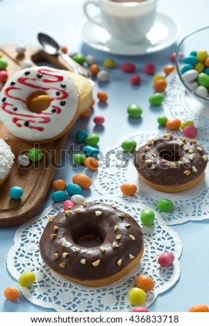 Delicious donuts with chocolate, coconut and strawberry. Served on the wooden board and white napkin. Decorated with multicolored candy and cup of coffee. Blue background. Vertical image.  - stock photo