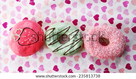 Delicious donuts with glaze on colorful paper background - stock photo