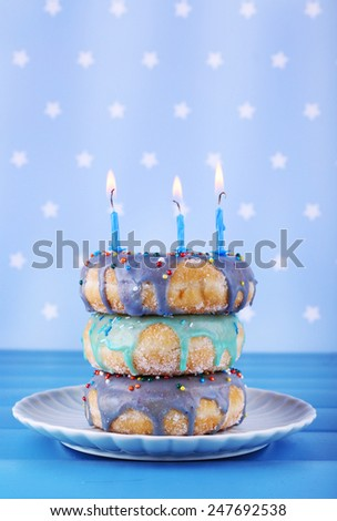 Delicious donuts with icing and birthday candles on table on bright background
