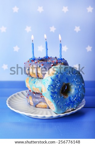 Delicious donuts with icing and birthday candles on table on bright background - stock photo