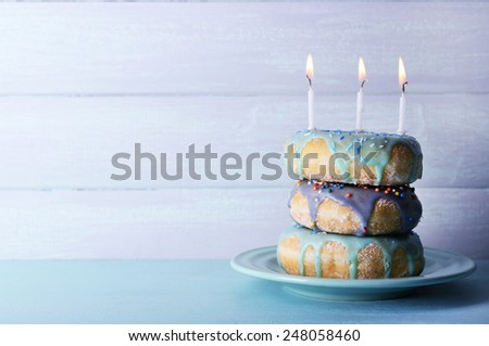 Delicious donuts with icing and birthday candles on table on wooden background - stock photo