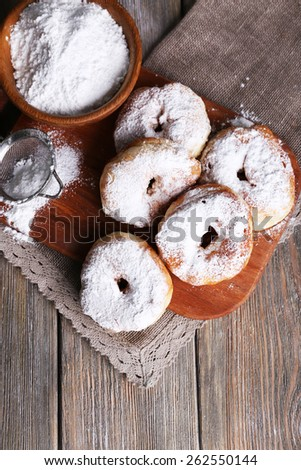 Delicious donuts with icing and powdered sugar on wooden background - stock photo