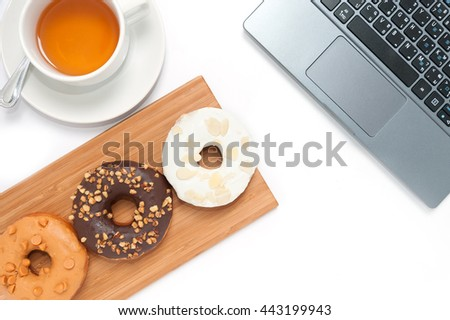 Delicious donuts with icing in wood plate and computer isolated on white