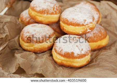 Delicious donuts with powdered sugar on parchment closeup - stock photo