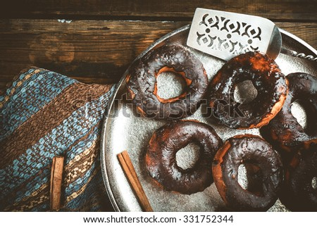 Delicious doughnuts with chocolate icing and cinnamon on table close up - stock photo