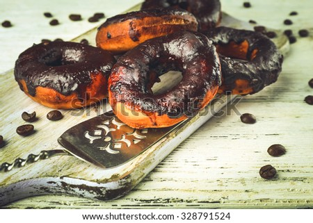 Delicious doughnuts with chocolate icing and coffee beans on table close up - stock photo