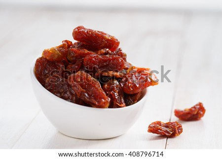 Delicious dried tomatoes in bowl on white wooden background.