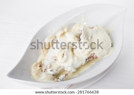 Delicious duck meat with potato dumplings covered with white sour cream sauce. Plate located on a white canvas tablecloth background.