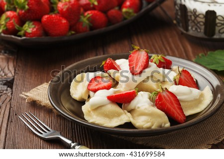 Delicious dumplings with fresh strawberries served with whipped cream and sugar. Dark wooden table as background. - stock photo