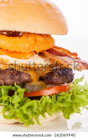 Delicious egg and bacon cheeseburger with a nutritional filling of salad ingredients, a ground beef patty, cheese, fried egg and crispy bacon on a white crusty roll - stock photo