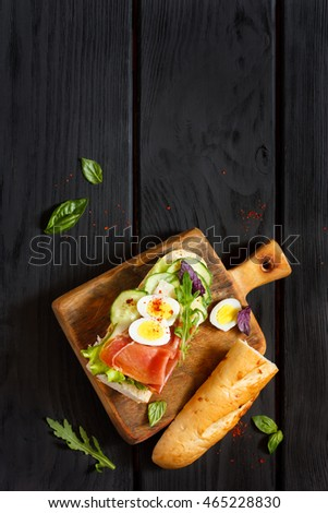 Delicious egg ham sandwich with greens on chopping board.