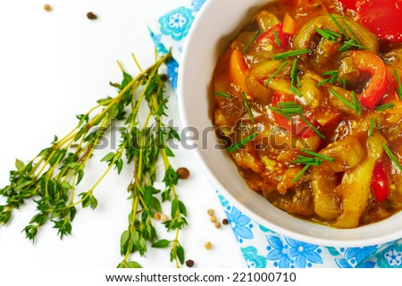 Delicious eggplant food with tomato, sweet pepper and fresh herbs and onion. Vegetarian food. - stock photo