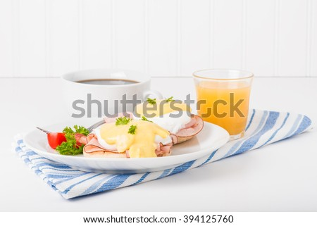Delicious eggs benedict served with fresh coffee and orange juice. - stock photo