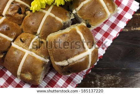 Delicious English style Happy Easter Hot Cross Buns tradition for Good Friday meal on dark vintage country style red check place mat setting with yellow Spring daisies. - stock photo