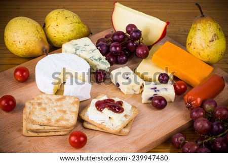Delicious festive cheese platter with crackers and grapes on wooden board for new years 2015. Rustic cheese selection with fruit and vegetables - stock photo