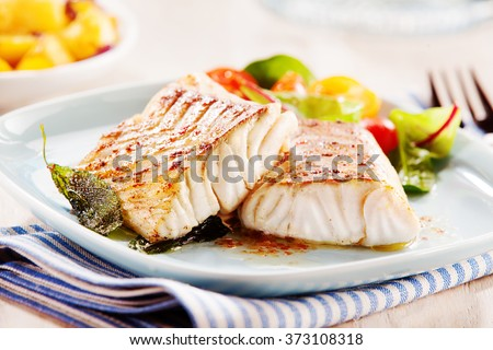 Delicious fillets of pollock or coalfish cooked in a spicy marinade and served with fresh salad and baby potatoes as a seafood appetizer to dinner - stock photo