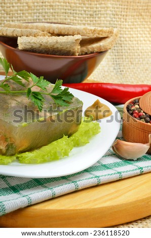 Delicious fish aspic on white plate with mustard and green salad - stock photo