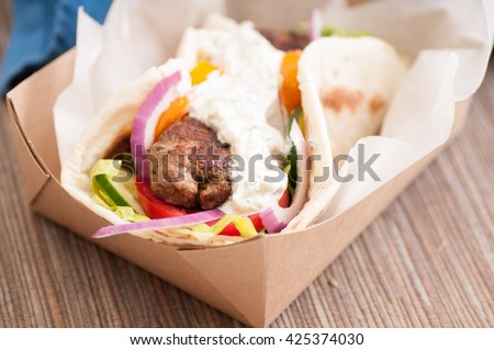 delicious flatbread wrap koobideh, iranian skewer with fresh vegetables and tzatziki sauce