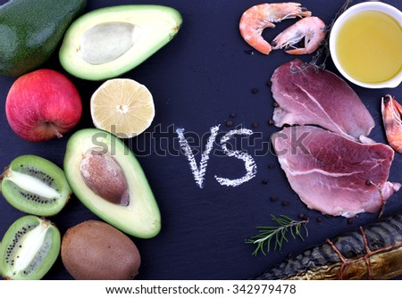 Delicious food composition of meat, seafood product with oil opposite vegetables and fruit, herbs on wet, black stone board background - stock photo