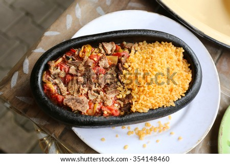 Delicious food in an iron skillet meat with rice - stock photo