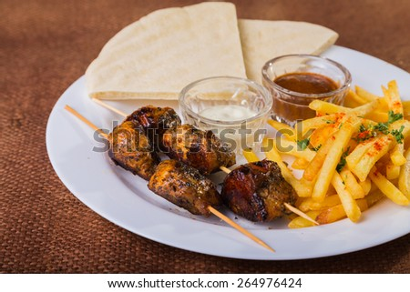 Delicious food. Meat with fries. Eastern food. Skewers of chicken and potatoes. The main dish. - stock photo