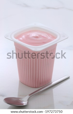 Delicious french custard-style yogurt with all the fruit mixed inside during the process. On vintage Italian carrara marble retro styling. - stock photo