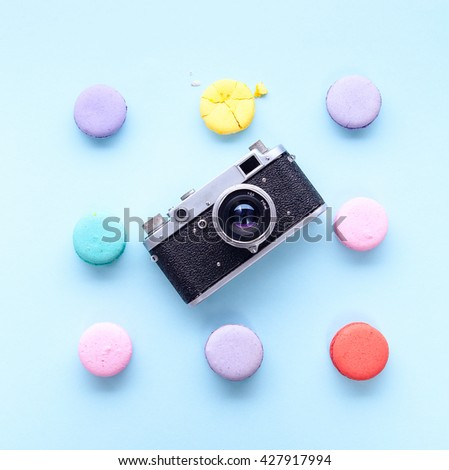 delicious French dessert macarons with vintage camera on a blue background - stock photo