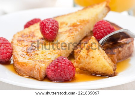 delicious French toast with raspberries and maple syrup, close-up