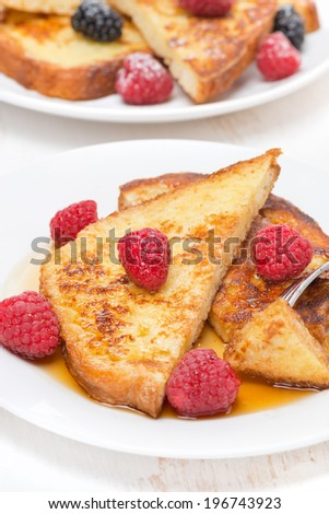 delicious French toast with raspberries and maple syrup, vertical, close-up