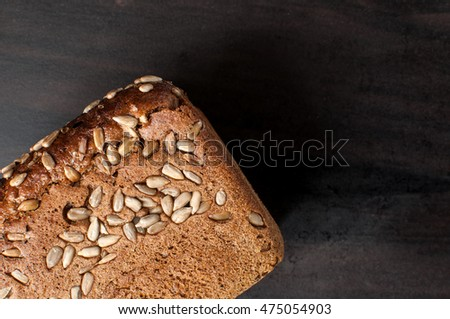 delicious fresh baked bread with bran sunflower seeds on a dark table, horizontal image