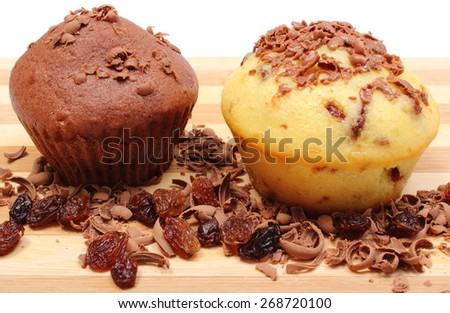 Delicious fresh baked muffins and grated chocolate with raisins lying on wooden cutting board - stock photo