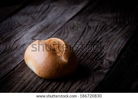 Delicious fresh baked roll. Bakery product photography taken on old wooden table.