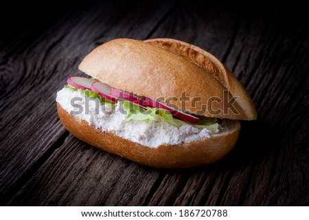 Delicious fresh baked roll. Bun sandwich served with creamy cottage cheese, lettuce and red radish slices  taken on old wooden table.