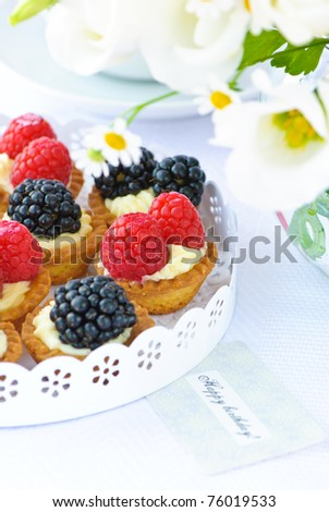 delicious fresh blackberry and raspberry cakes with protein cream and a white spring flowers