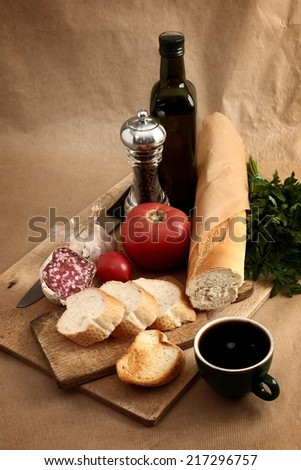 delicious fresh bread, vegetables, salami and black coffee for breakfast
