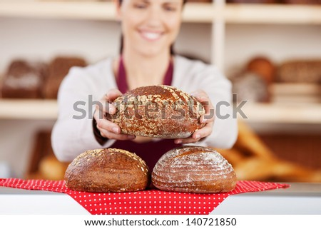 Delicious fresh crusty loaves of bread on a bakery counter with a female assistant holding one in her hands - stock photo