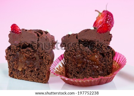 Delicious fresh cut chocolate cupcake with caramel - stock photo