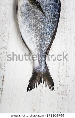 Delicious fresh dorado fish on wooden kitchen board - stock photo