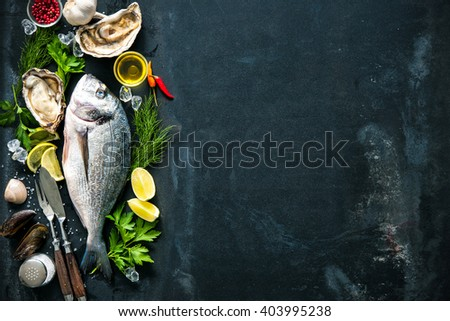 Delicious fresh fish and oysters with aromatic herbs, spices and vegetables on dark slate plate - stock photo